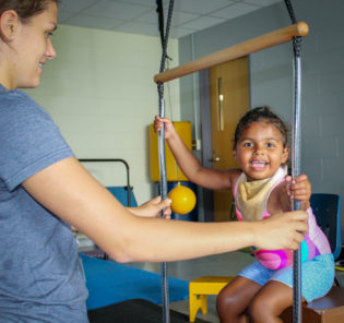 Esmae Smiling while receiving Physical Therapy - Esmae receives therapy from Racker's Physical Therapist in Ithaca